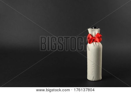 Wine bottle in gift bag on dark background