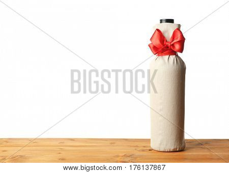 Table with wine bottle in gift bag on white background