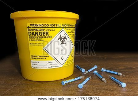 Used Needles laying next to a sharps bin
