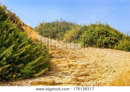 Stone trail in mountain dangerous path to top of stone landslides. Dense green bushes grow on the mountain shale rocks. Tourist beach resort in village of Bali Crete island Greece Beach Caves