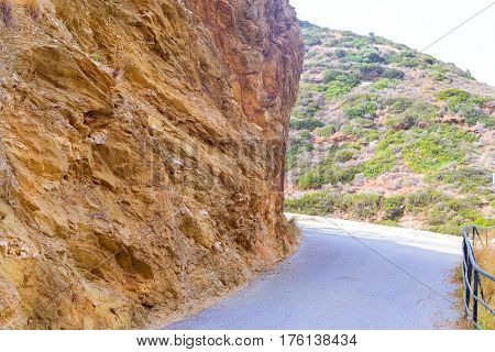 Mountain road cut through rock. Slice mountain shale texture of stone mountain wall. Stone trail in mountain dangerous path to top of stone landslides. Village Bali Crete island Greece