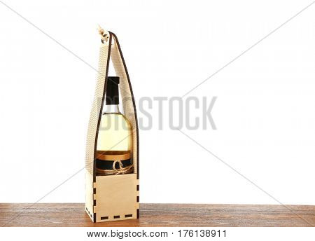 Table with wine bottle in gift box on white background