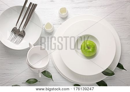 Set of dinnerware with apple on white wooden table