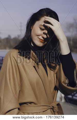 stylish young woman out for a walk. she dressed and looks very fashionable. coat of beige (camel) color and black turtleneck. beautiful woman. the portrait she smiles.