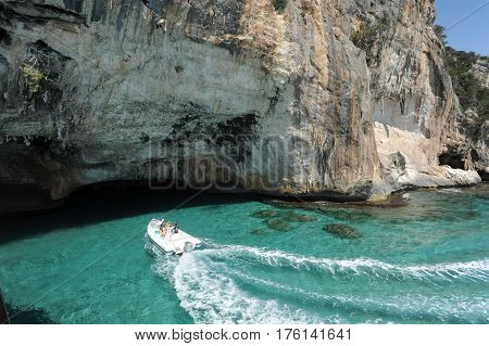 Bue Marino, Italy - 28 June 2013: people on a motorboat visiting the cave of Bue Marino on the island of Sardinia, Italy
