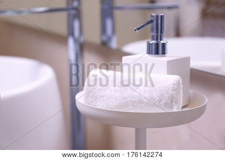 Soap dispenser and towel in modern spa salon