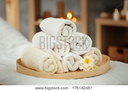 Wooden tray with pile of towels in spa salon