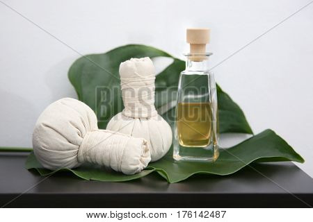 Herbal compress balls and natural oil on green leaf