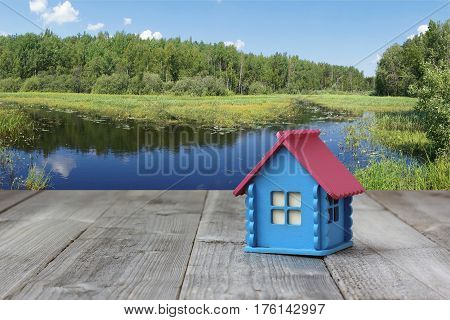 small blue wooden house on the river and the forest. cottage in the woods on the shore .