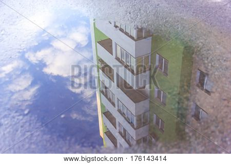 Water reflection house in the puddle. Apartment building is reflected in the water. The forms of objects distorted