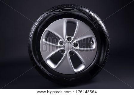 Modern car wheel on black background