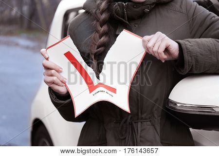 Happy young woman tearing learner driver sign while standing near car outdoors, closeup