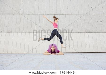 young healthy woman jumping across an interacial friend on the floor