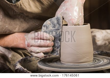 Creating mug from clay on a twisted potter's wheel. Dirty hands in the clay and the potter's wheel with the workpiece. The sculptor in the workshop makes a jug out of earthenware.