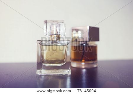Two bottles of perfume on the table. The concept of perfume and luxury. Fragrant perfume.