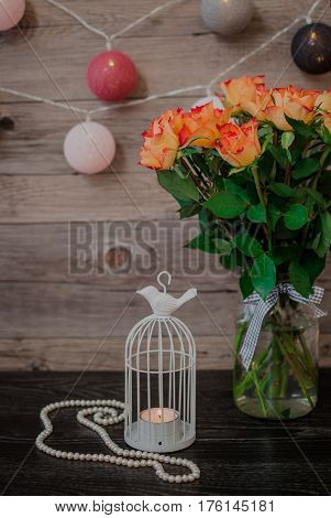 Fresh orange roses in vase. A beautiful white pearl necklace. Garland in the form of balls, wrapped in colored thread. Little white candlestick.
