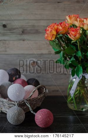 Wicker basket with garland in the form of balls, wrapped in colored thread. Orange roses on a wooden background.