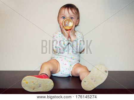 The infant drinks from a baby bottle. Little hands grasped the bottle. Large children's eyes. Baby in a diaper.
