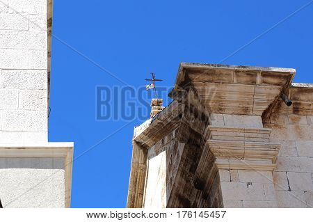 This is a small simple barely visible cross which is set above the entrance to one of the old Croatian churches.