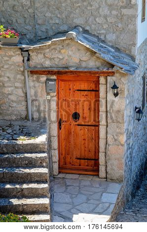 Wooden door and stone house in Pocitelj