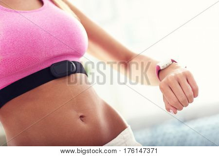 Sports woman using smart watch and checking her heart rate