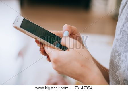 Young beautiful hipster girl with mobile phone in hands is looking in camera, while is sitting on a river jetty against blurred buildings with copy space for your advertising text message or content