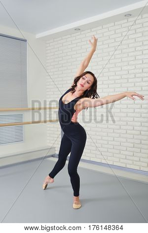 Beautiful woman dancer in black bodysuit gracefully dancing ballet at studio.