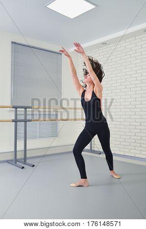 Beautiful woman in black bodysuit dancing ballet at studio, shoot in motion.
