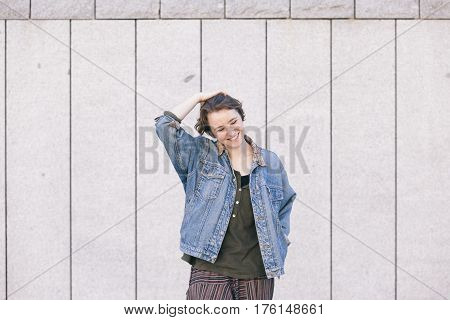 cheerful young teen woman standing on the street with hapiness and a positive attitude isolated on a grey wall