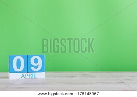 April 9th. Day 9 of month, calendar on wooden table and green background. Spring time, empty space for text.