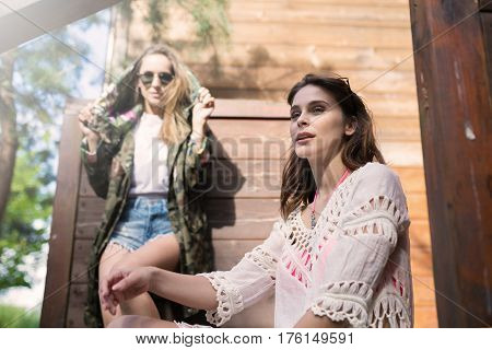 Girl Sitting Outside Wooden Cabinet With Friend