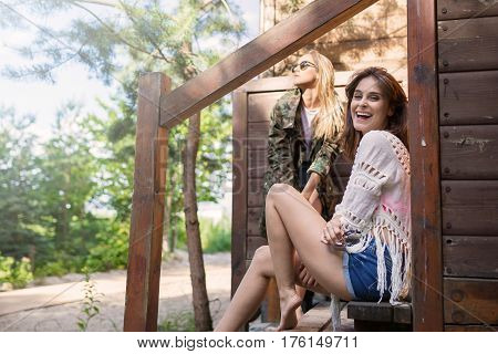 Young Laughing Woman Sitting On Stairs With Her Friend