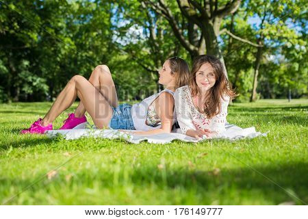 Two Beautiful Women Lying On Blanket Outside