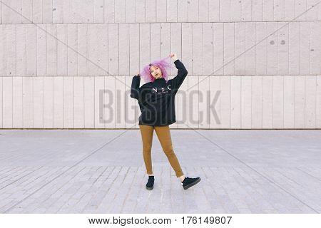 beautiful mixed race woman with Brooklyn attitude isolated on a grey wall