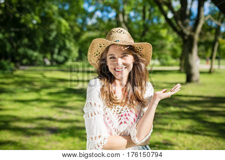 Carefree girl in hat posing in park