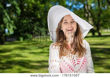 Beautiful Woman In Hat Standing In Park Laughing