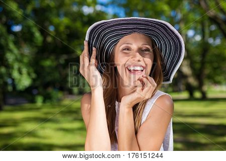 Young joyful woman holding hat in park