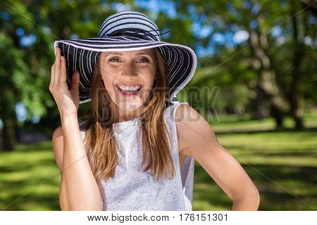 Beautiful Happy Woman Holding Hat Standing Outside