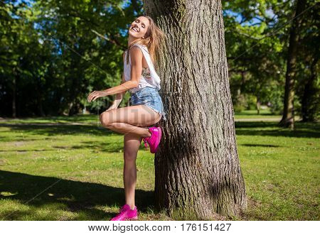 Beautiful girl leaning against tree in park and laughing