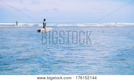 Silhouette of Fit woman going to surf in sea and looking to wave edge on horizon at Bali island, Indonesia.