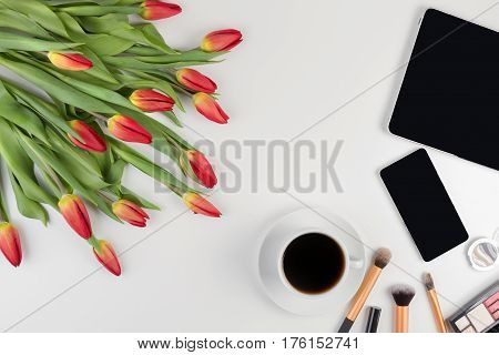 Creative beauty feminine background with flowers, coffe and make up tools, cosmetics. Flat lay. Top view