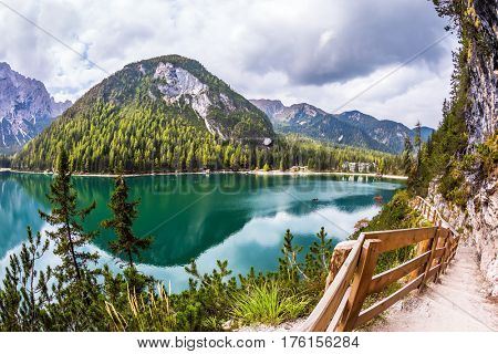 The footpath around the lake is fenced with a wooden handrail. Magnificent Alpine lake Lago di Braies. Concept of ecological and pedestrian tourism