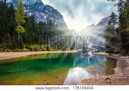 Magnificent lake in South Tyrol, Italy. Sunshine on autumn day. The concept of walking and eco-tourism. Water reflects the surrounding mountains and forest
