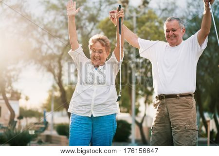 senior couple celebrating playing miniature golf