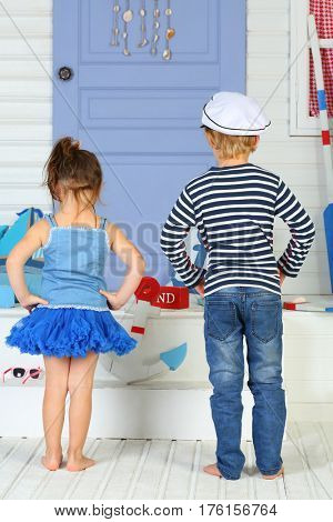 A boy in striped vest and white cap and little girl standing back in front of the porch with lilac door