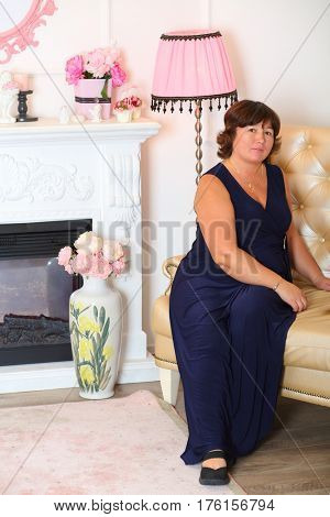 Woman in long black dress sitting on a sofa near pink floor lamp and fireplace in the living room