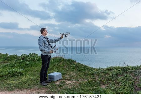 Man pilot, holds the drone before the flight. For video on the sea.