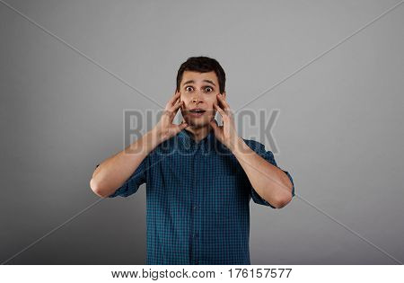 Scared man in plaid blue shirt. Portrait of Shocked emotion. Handsome guy holding head with both hands over grey background. Person have seen something dangerous. Bad news concept.