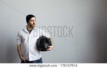 Extreme rider in white shirt standing over grey wall with black motorcycle helmet. Tourist biker before new trip in studio. Copy space for advertising motor goods or promotional text.
