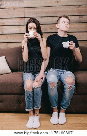shy guy flirts with the girl. They are sitting on a brown sofa at home. The concept of the first love relations